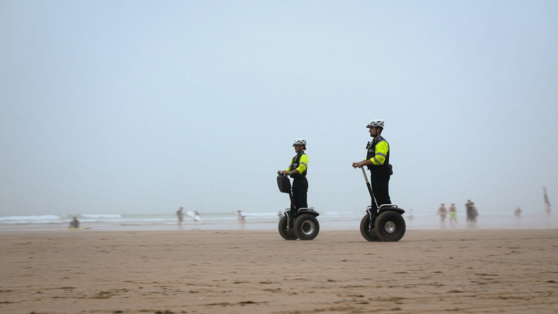 devon and cornwall cops - police man and woman riding segways on beach