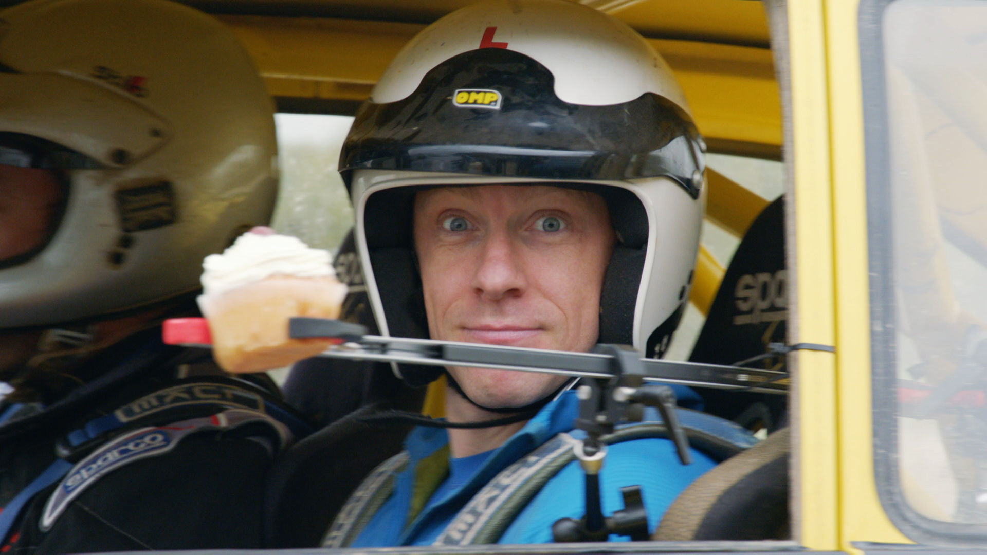 CBBC Beyond Bionic - Andy Torbet in a racing car with a cupcake on a stick