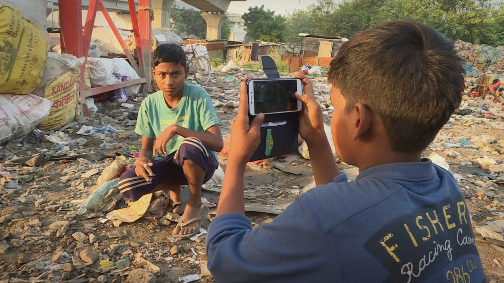 Young reporter talking picture of friend at rubbish dump